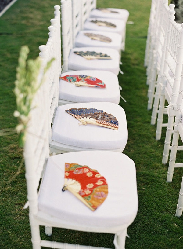 Brightly coloured fans placed on each chair at the wedding ceremony as a wedding favor for guests | Vicki Grafton Photography via Style Me Pretty