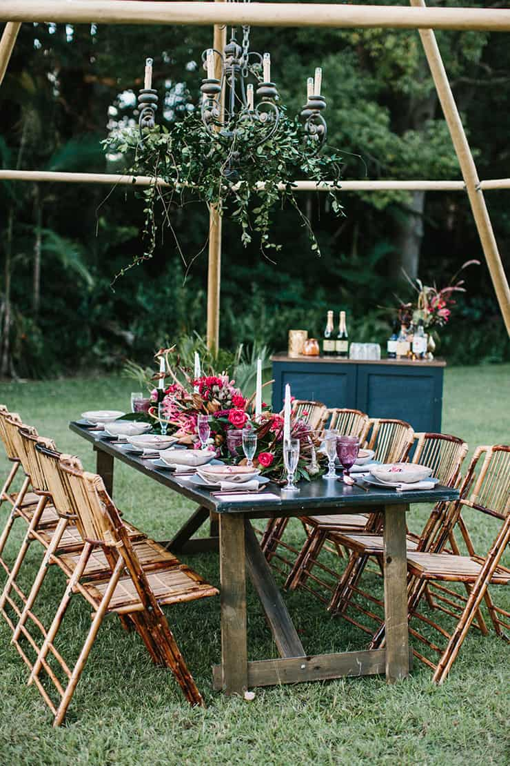 Bohemian berry outdoor wedding reception setting with a greenery draped chandelier | Camilla Kirk Photography