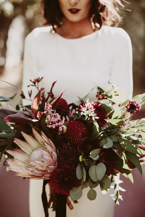 Bohemian burgundy Protea wedding bouquet | Lauren Scotti Photography via Junebug Weddings