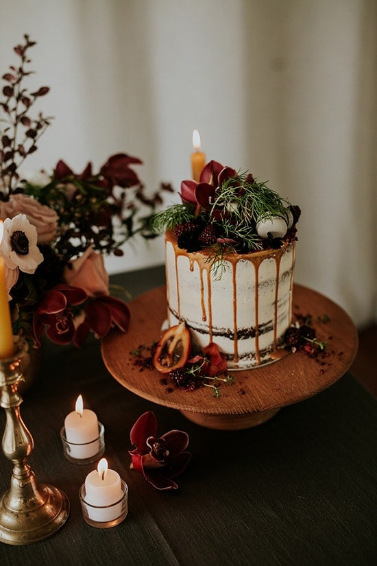 Bohemian wedding cake with caramel drip and burgundy flowers | Amy Kate Photography via Paper & Lace