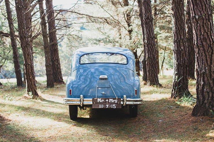 Blue vintage wedding getaway car in woodland setting