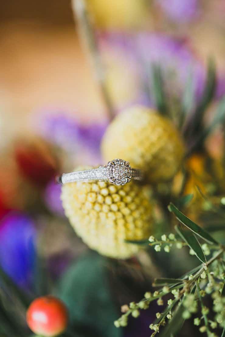 Vintage wedding ring on bright wildflower bouquet