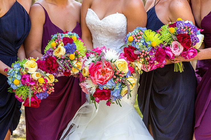 Navy and purple bridesmaid dresses with bright bouquets