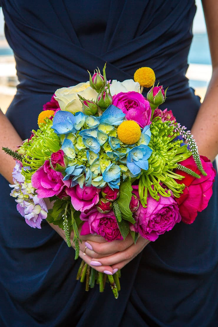 Navy bridesmaid dress and bright bouquet for beach wedding