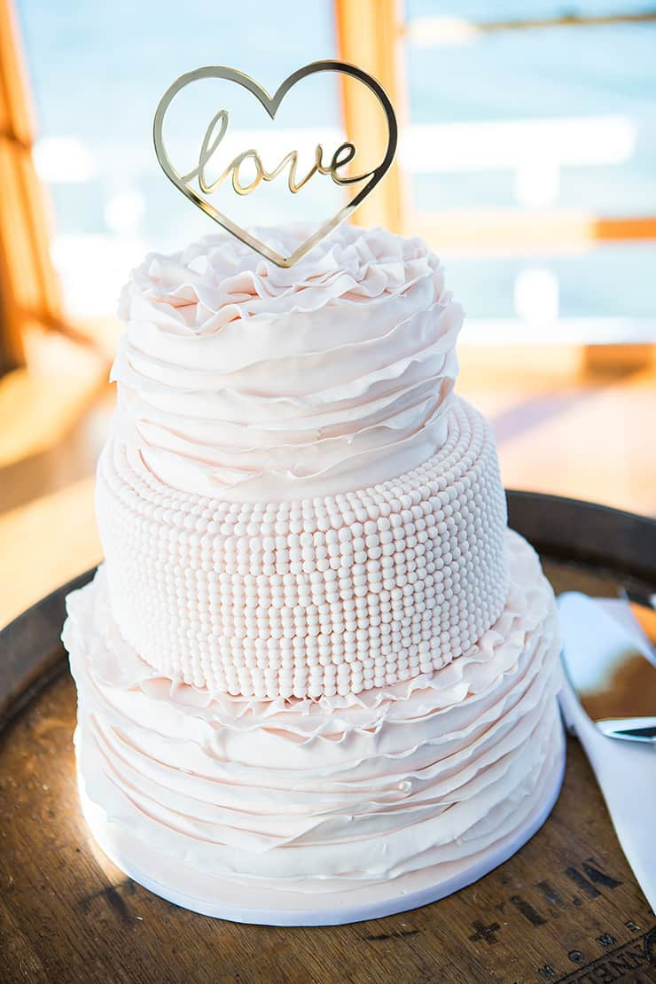 Classic white wedding cake with ruffles and pearl detail