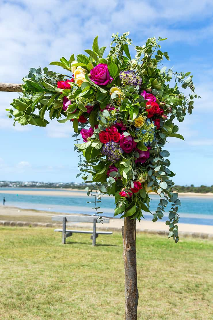Rustic arbour with bright flowers for beach wedding ceremony
