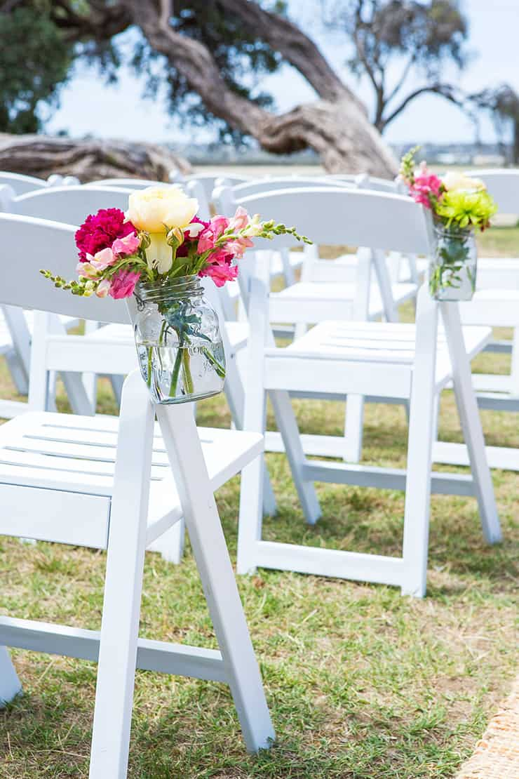 Jars of bright flowers tied to white chairs for beach wedding ceremony