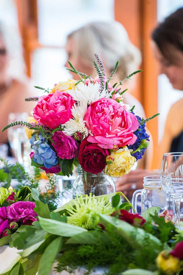 Bright wedding bouquet used as centrepiece on bridal table