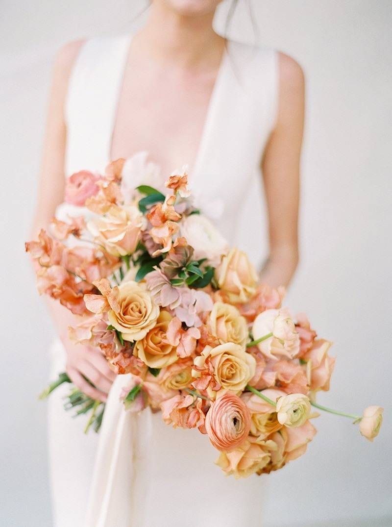 Romantic Boho Desert Pastel Wedding Ideas | A modern romantic asymmetrical wedding bouquet featuring pale yellow roses, peach ranunculus, salmon pink bougainvillea and blush hellebores tied with white flowing ribbon. No greenery is used to make this warm colour palette pop. | Photography: Ashley Ludaescher