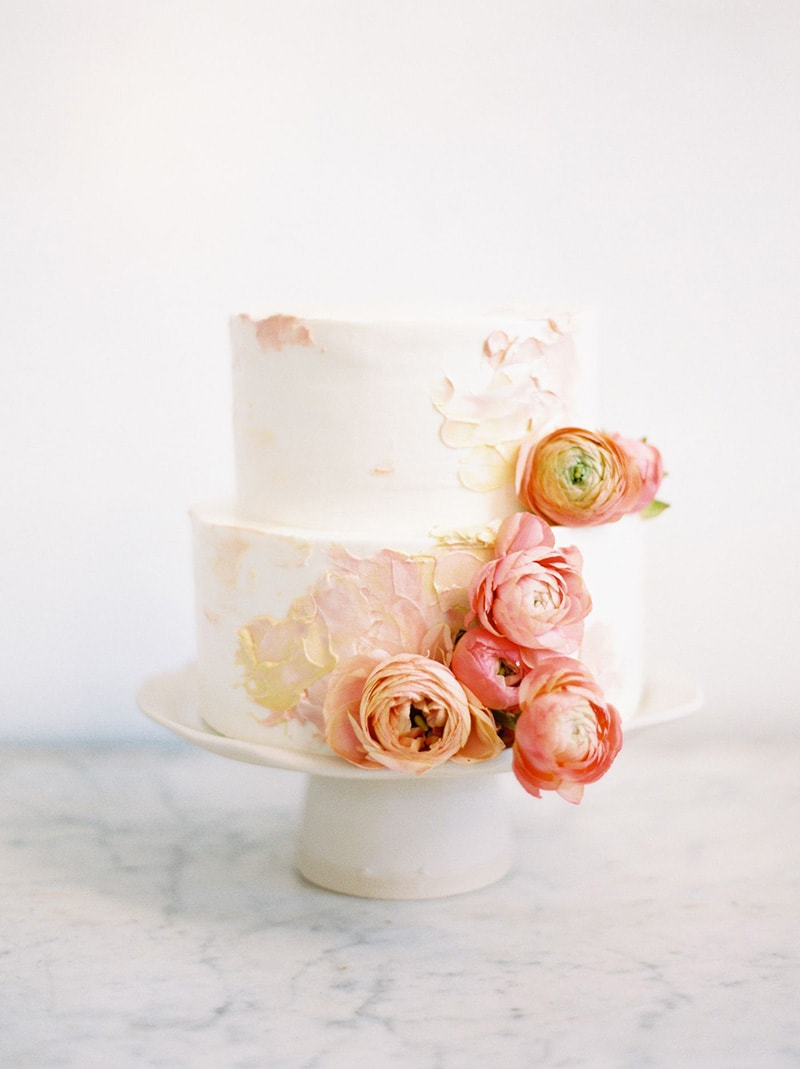 Romantic Boho Desert Pastel Wedding Ideas | A elegant two tier buttercream wedding cake decorated with palette knife painted detail in pale blush and yellow tones and cascading salmon pink and peach ranunculus. | Photography: Ciara Richardson via Once Wed