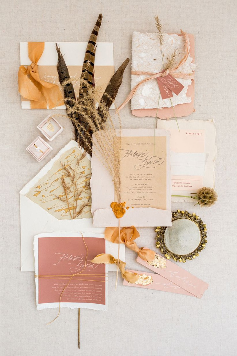 Romantic Boho Desert Pastel Wedding Ideas | Eclectic boho wedding stationery suite featuring modern fine line script on deckle edge handmade cotton paper in blush, dusty pink, terracotta and sand tones, finished with ribbon, raffia, gold foil, wax seals and sprigs of dried foliage. | Photography: Kir2Ben via Wedding Wire