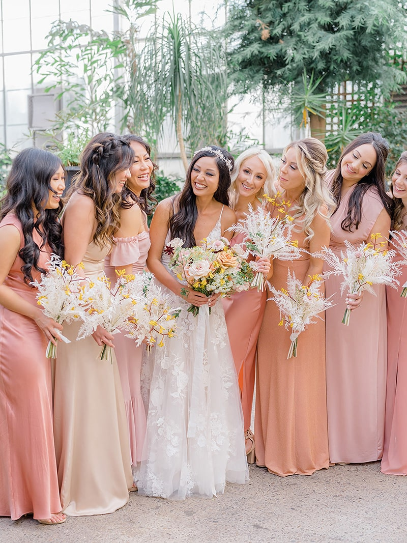 Romantic Boho Desert Pastel Wedding Ideas | Floor length mismatched romantic boho bridesmaid dresses in pink, peach and ivory tones. The bridal party wear their hair in crown braids and loose waves and carry sprays of white dried ruscus and fern paired with yellow kangaroo paw. The bride in the centre of the group wears a tulle wedding dress with spaghetti straps and floral lace applique, a white beaded circlet headpiece and boho waves. She carries a larger bouquet with added roses and other delicate blooms. | Photography: Magdalena Studios via Belovely Floral Co.