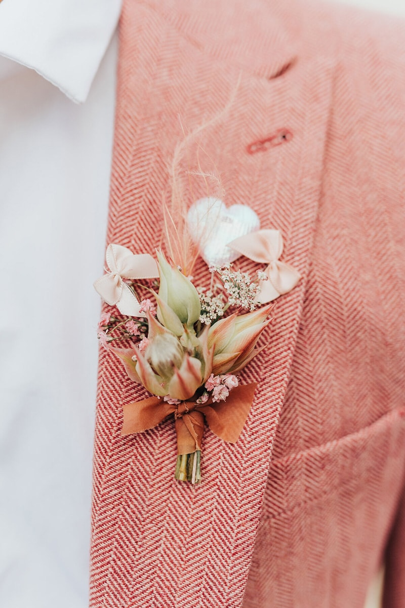 Romantic Boho Desert Pastel Wedding Ideas | Coral pink wedding suit for the groom featuring a bold chevron pattern and a blushing bride boutonniere tied with terracotta ribbon. Photography: Rebecca Carpenter via The Stars Inside