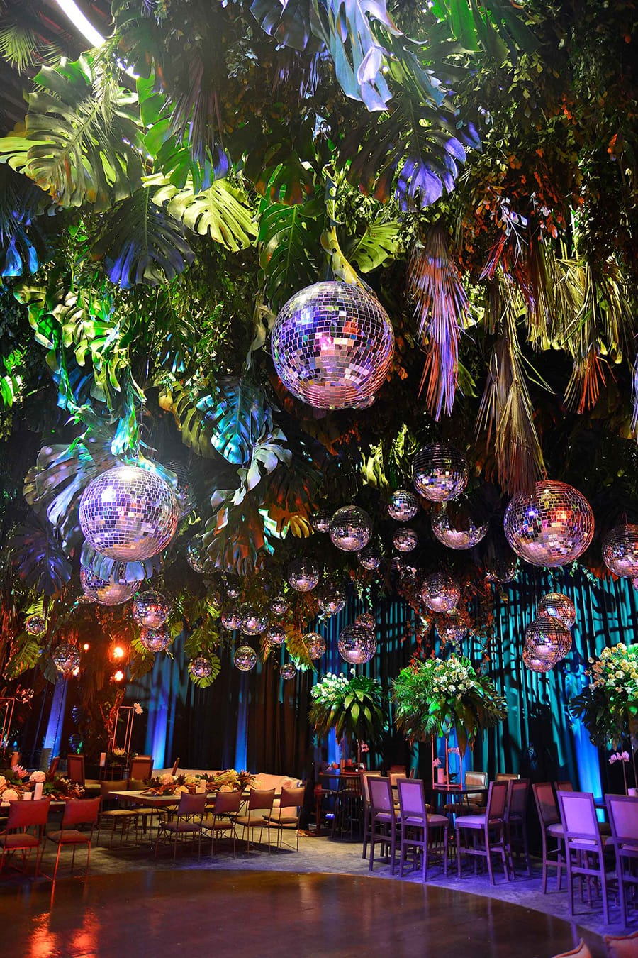 Electric Disco Wedding Ideas |  Modern greenery installation at a wedding reception suspended above the dance floor featuring tropical leaves, palm fronds and dozens of mirror balls of all different sizes | Photography: Ana Hinojosa & Sergio Sandona via Brides