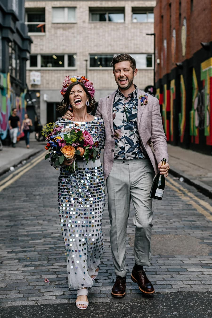 Electric Disco Wedding Ideas |  A bride and groom laugh as they walk down an urban industrial cobbled street with graffic art on the walls. The bride wears a shimmering silver sequin wedding dress. She carries a bright multicolour wedding bouquet and wears a matching flower crown. The groom wears grey pants, muted pink jacket and a tropical print shirt. He carries an open bottle of champagne. | Photography: Epic Love Story