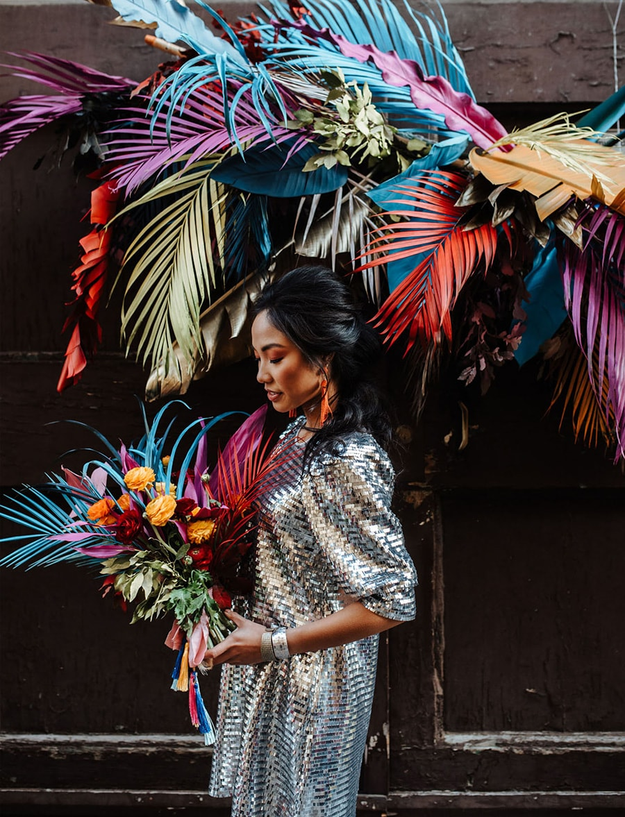 Electric Disco Wedding Ideas |  Suspended wedding ceremony backdrop featuring a cluster of palm fronds and tropical greenery spray painted in bright neon colours. A bride stands in front of the installation wearing a silver mirror ball inspired wedding dress and holding a bright tropical wedding bouquet to match the backdrop | Photography: Silvia Galora Photography via Green Wedding Shoes