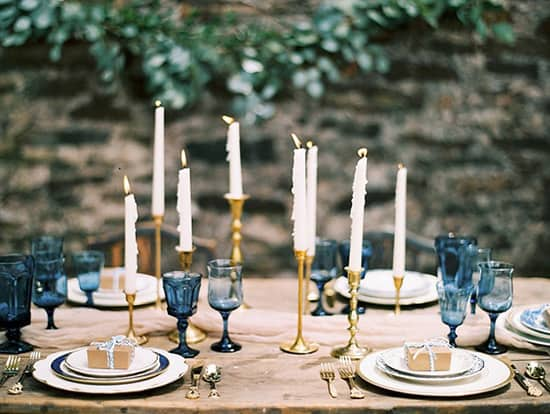Wedding reception centrepiece with gold candlesticks and blue glassware | Anna K. Photography via Southern Weddings