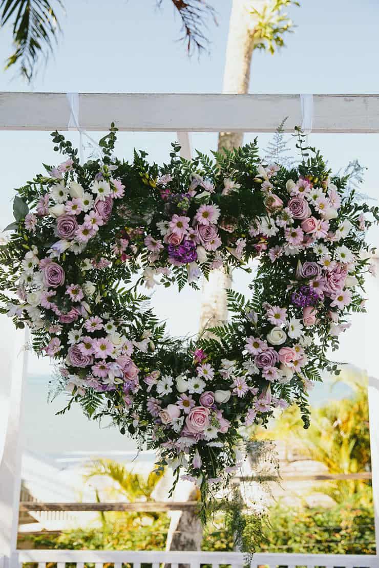 Elegant-Tropical-Wedding-Ceremony-Purple-Flower-Heart-Wreath-Backdrop