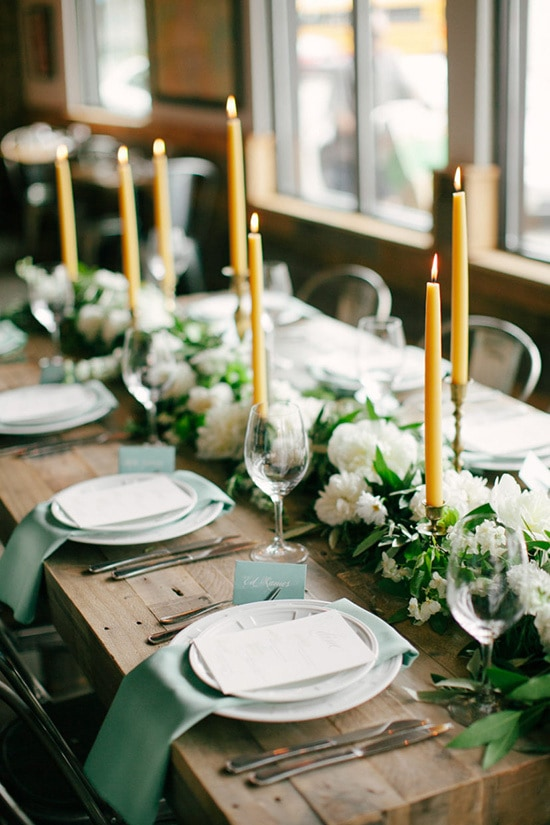 Rustic reception centrepiece with mustard yellow candlesticks and green and white floral table runner | Laura Ivanova via Style Me Pretty