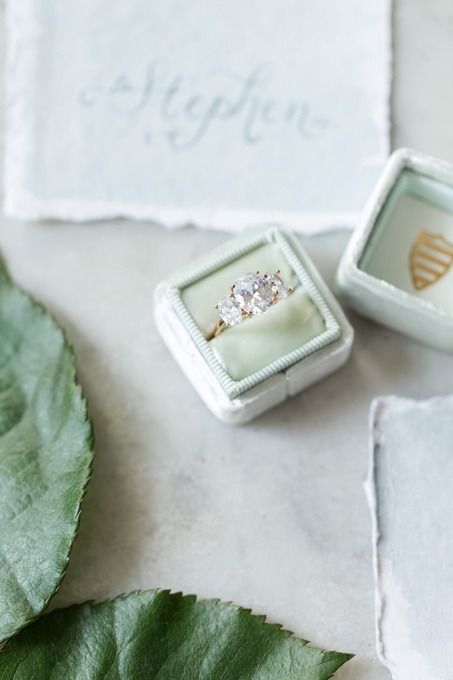 Yellow gold oval diamond trilogy engagement ring displayed in green velvet ring box | Photography: Camille Catherine Photography via Elizabeth Anne Designs