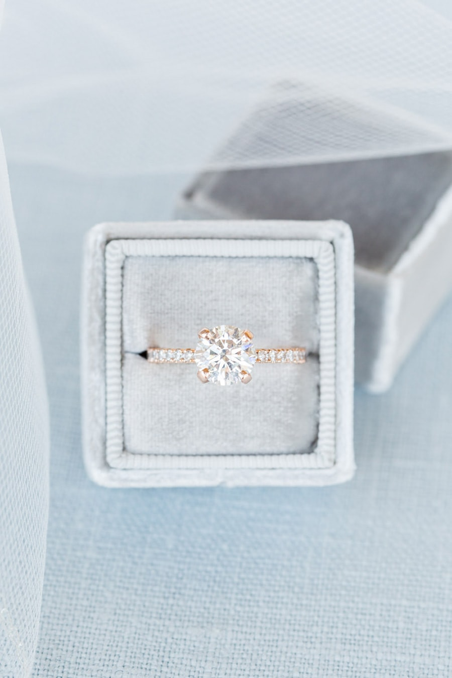 Rose gold solitaire diamond engagement ring with pave band displayed in grey velvet ring box | Photography: Cavin Elizabeth Photography
