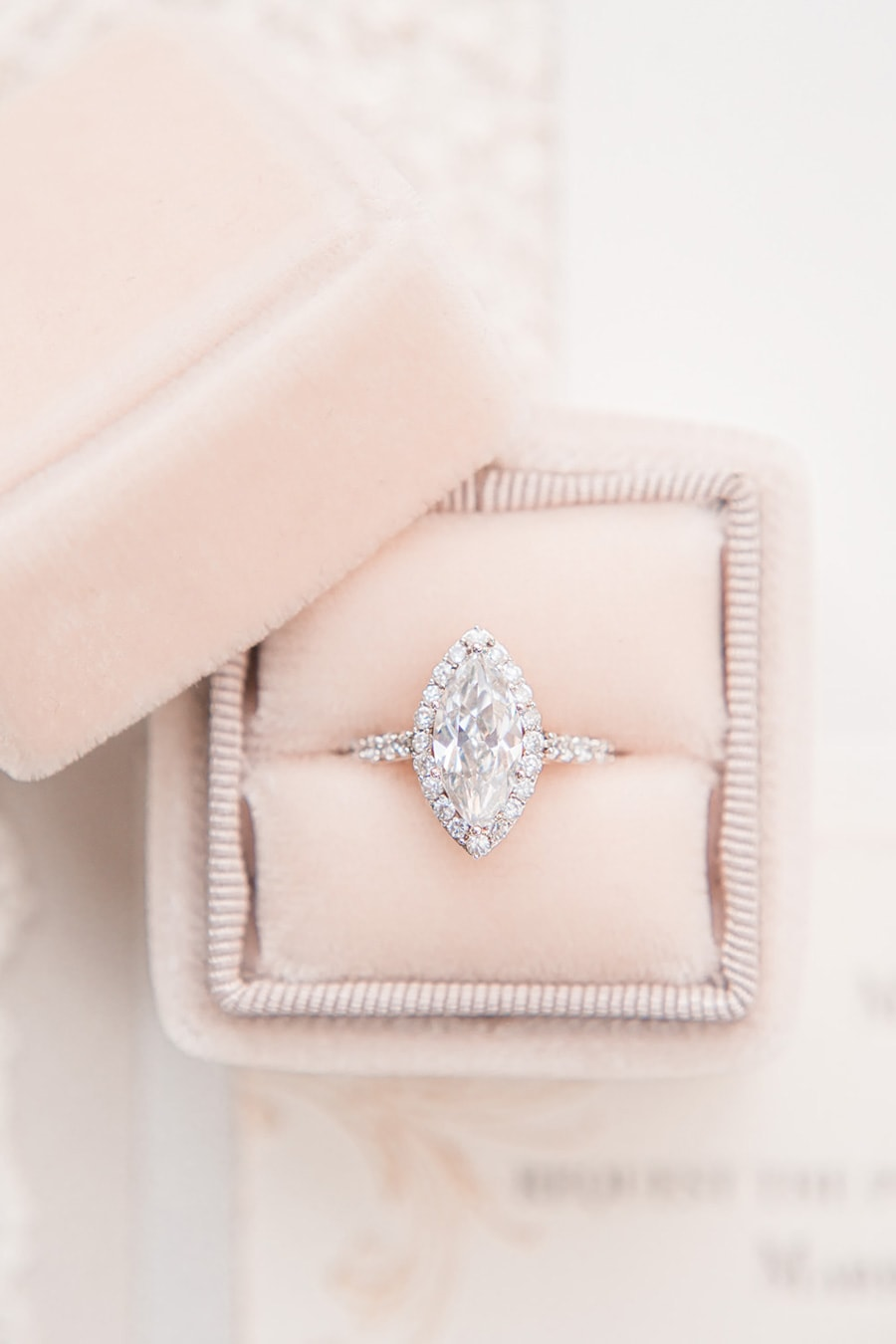 Rose gold marquise halo diamond engagement ring with pave band displayed in blush velvet ring box | Photography: Joanna Briggs Photography via Whimsical Wonderland Weddings