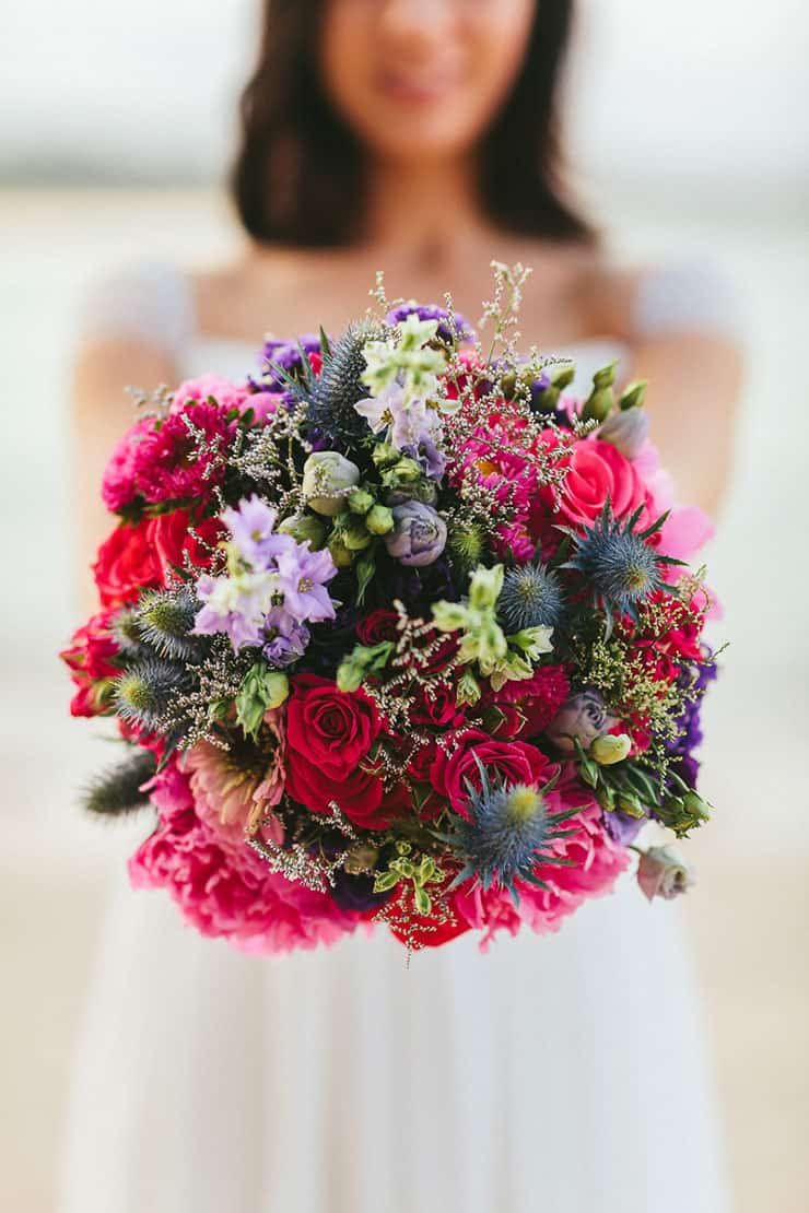 Bright and modern wedding bouquet with pink roses and blue thistle
