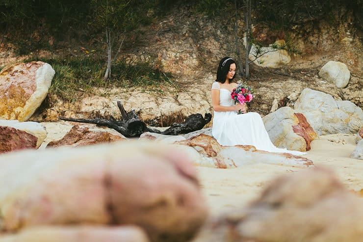 Bride sitting on beach with bright bouquet