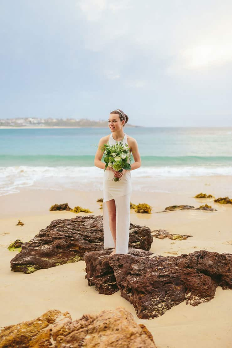 Modern beach bride holding green and white wedding bouquet