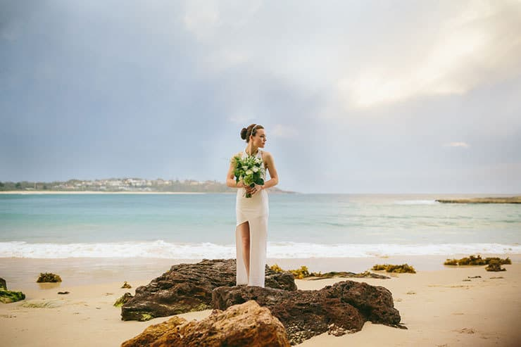 Bride in modern asymmetrical wedding dress standing on beach with bouquet