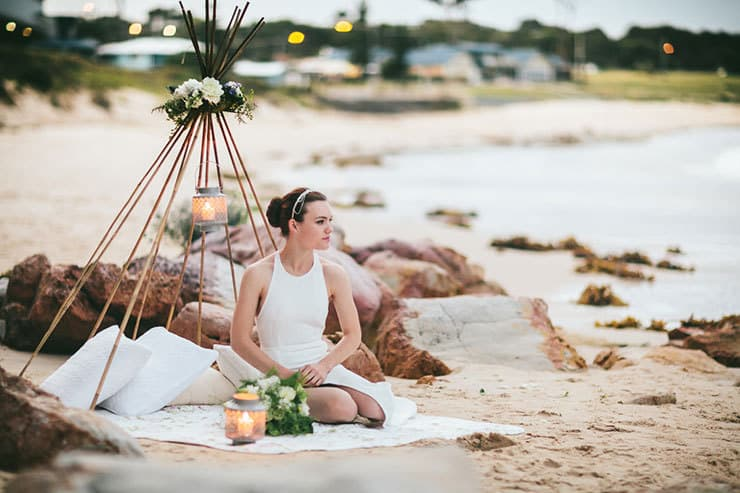 Modern bride sitting in beach wedding teepee