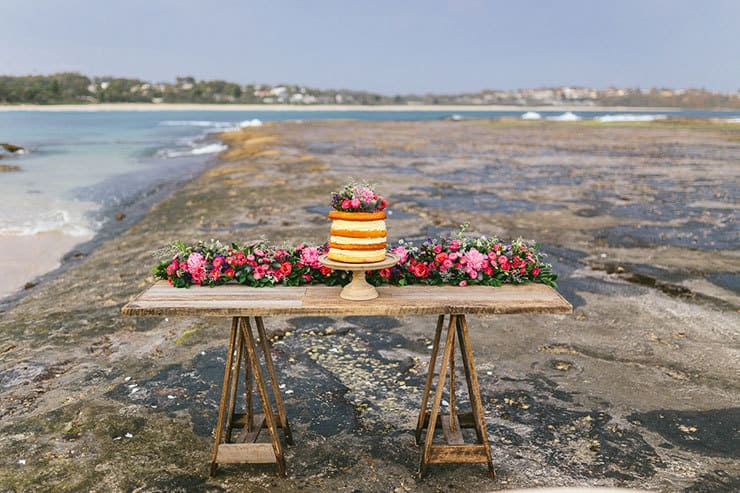 Naked wedding cake on beachside reception table