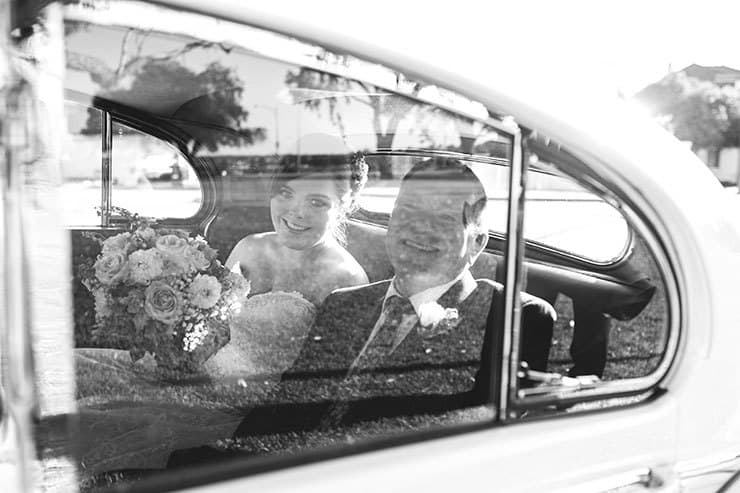Bride and father arriving by vintage car
