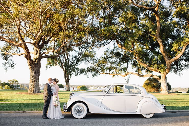Bride and groom with white vintage car
