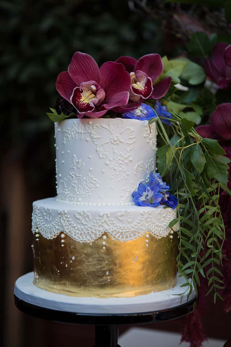 White fondant wedding cake with gold foil and burgundy orchids | Lola Images