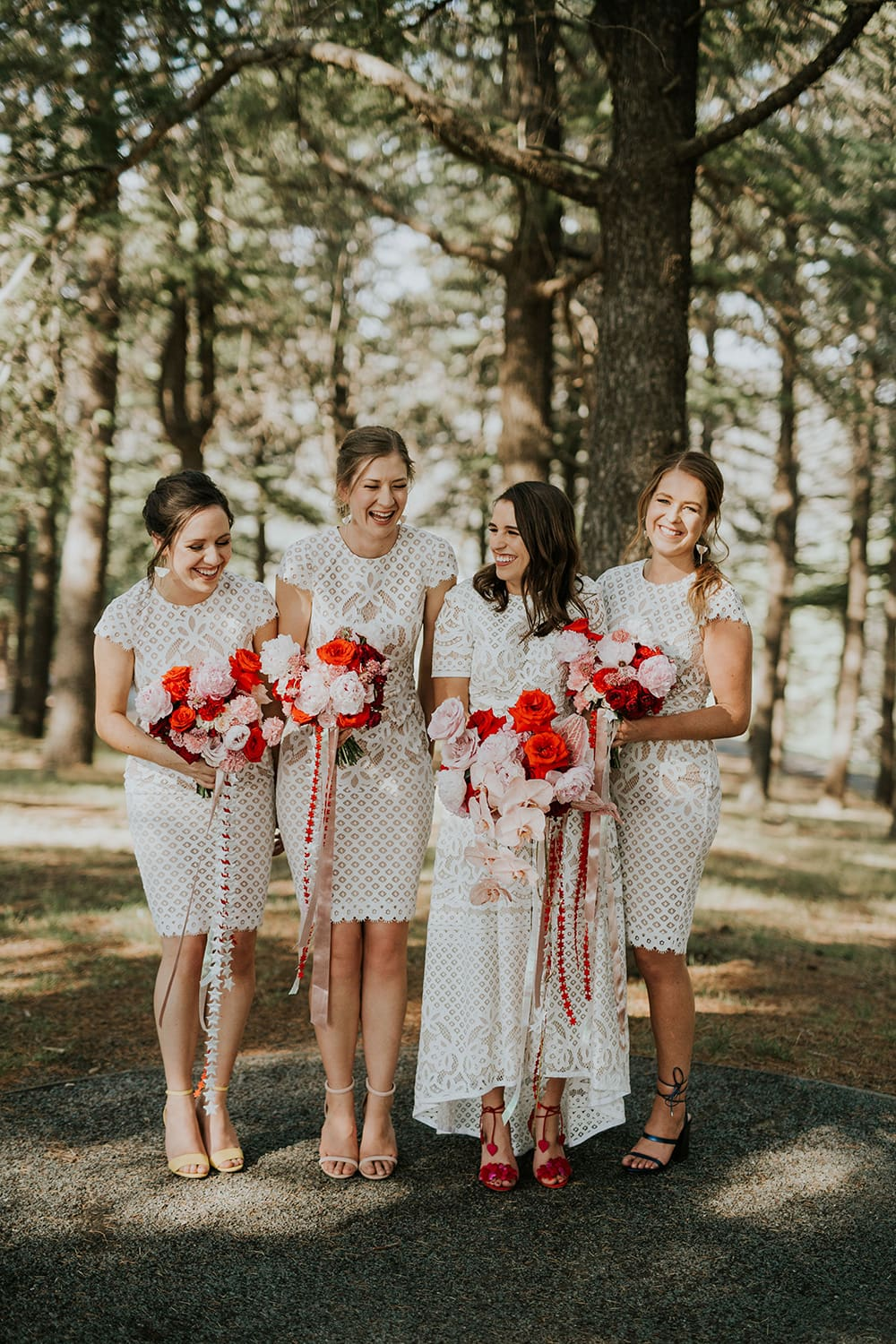 Modern Red & Pink Wedding Ideas | White lace bride and bridesmaid dresses paired with pink and red bouquets featuring roses, orchids and trailing ribbons | Photography: Alana Taylor Photography via Hello May