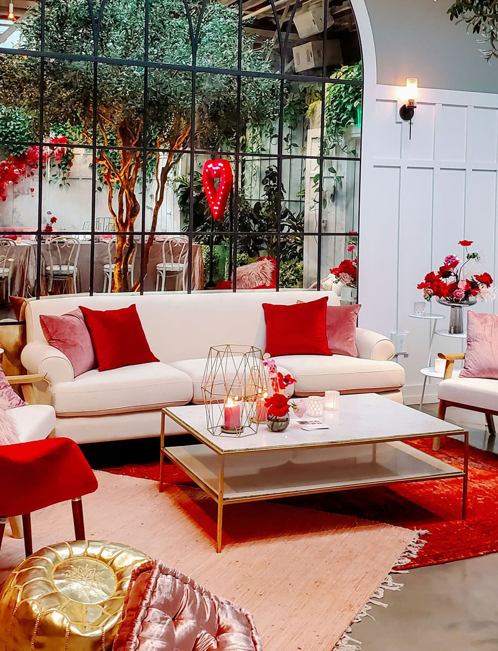 Modern Red & Pink Wedding Ideas | A modern wedding reception lounge setting featuring a white lounge decorated with red and pink pillows, a white coffee table with gold edges topped with candles and layered pink and red rugs. | Photography: Madeline Kate Photography via Together Journal