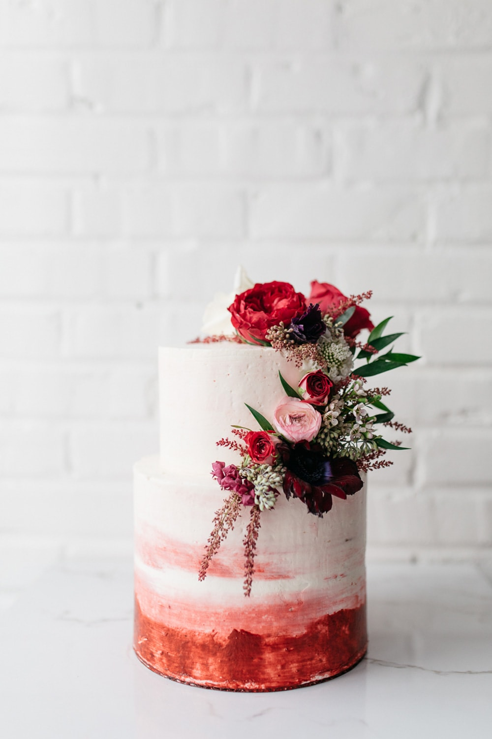 Modern Red & Pink Wedding Ideas | A rustic two tier white buttercream wedding cake with a cascade of red, pink and white flowers on the top tier and red and pink watercolour detail on the bottom tier. | Photography: Carrie Mcguire via Green Wedding Shoes