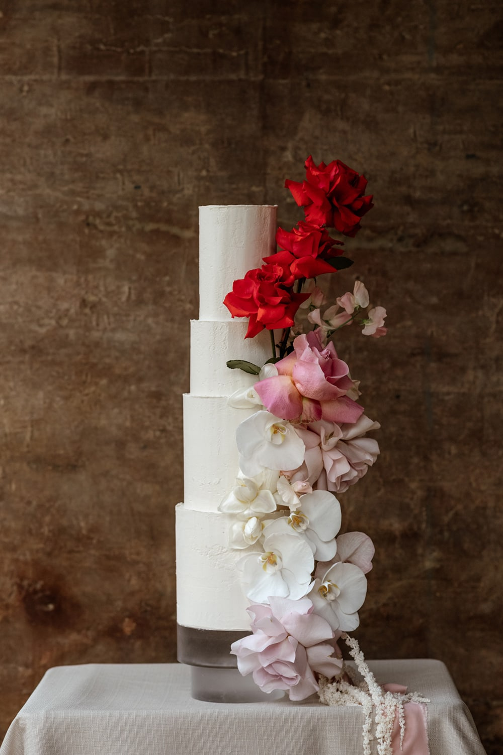 Modern Red & Pink Wedding Ideas | An elegant four tier wedding cake in white buttercream topped with cascading ombre florals in red, pink and white, including roses, orchids, sweet pea and amaranthus. | Photography: Laura Martha Photography via Bridal Musings
