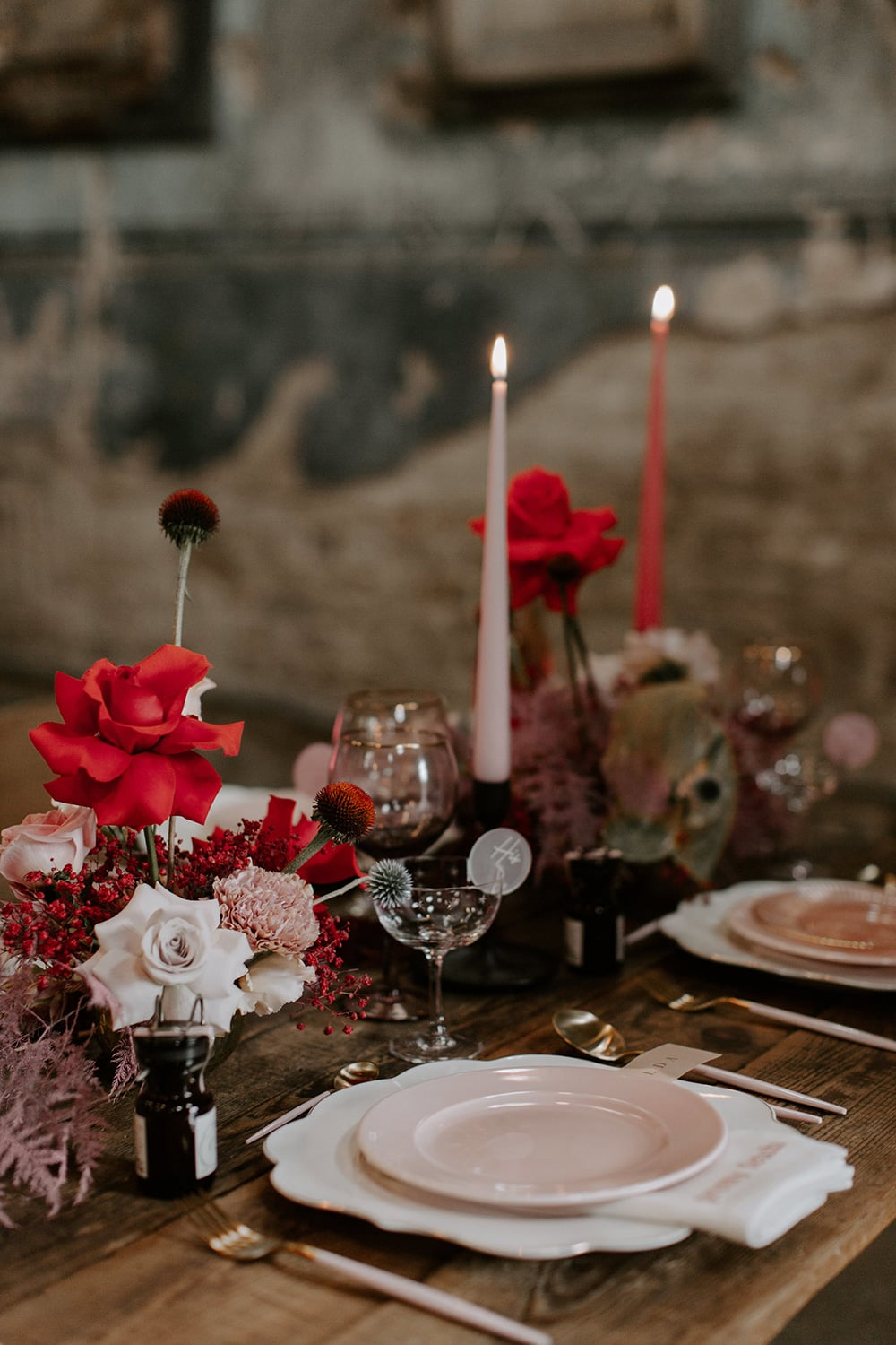 Modern Red & Pink Wedding Ideas | A modern industrial wedding reception table setting on a bare wood table features layered blush and white tableware, artful red and pink flower arrangements and tonal taper candles to match. | Photography: Emily Rose Photography via The Stars Inside