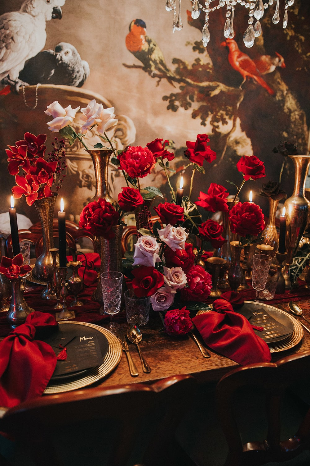Modern Red & Pink Wedding Ideas | A moody candlelit wedding reception table setting in front of an ornate wall art which features illustrations of exotic birds. The table is decorated with gold vessels of different shapes and sizes filled with clusters of red and pink flowers, gold charger plates and cutlery, black taper candles, plateware and menus, crystal glassware and knotted red napkins. | Photography: White Fox Studios via The Wedding Playbook