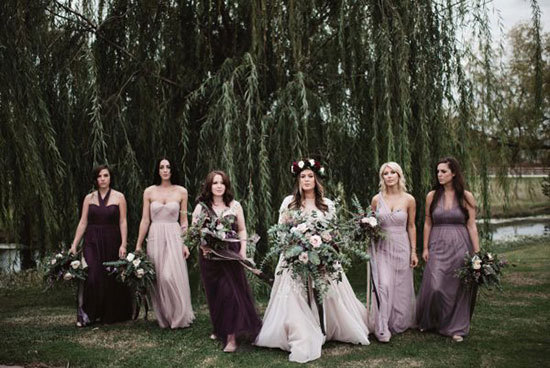 Modern romantic bride and bridesmaids wearing mismatched dresses in shades of purple | A Sea of Love via Junebug Weddings