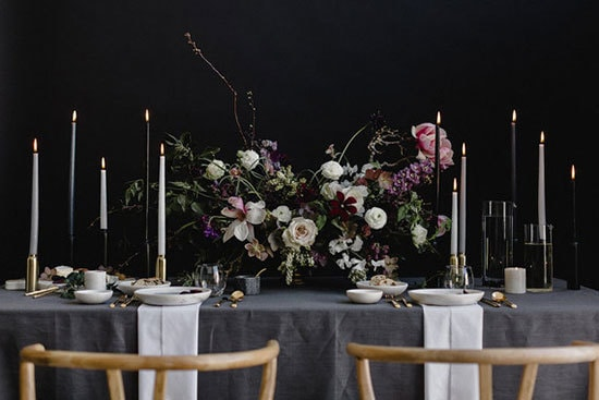 Moody botanical wedding reception table setting with grey linen, centrepiece featuring white, pink and purple flowers and candlesticks on a black backdrop | A Sea of Love via 100 Layer Cake