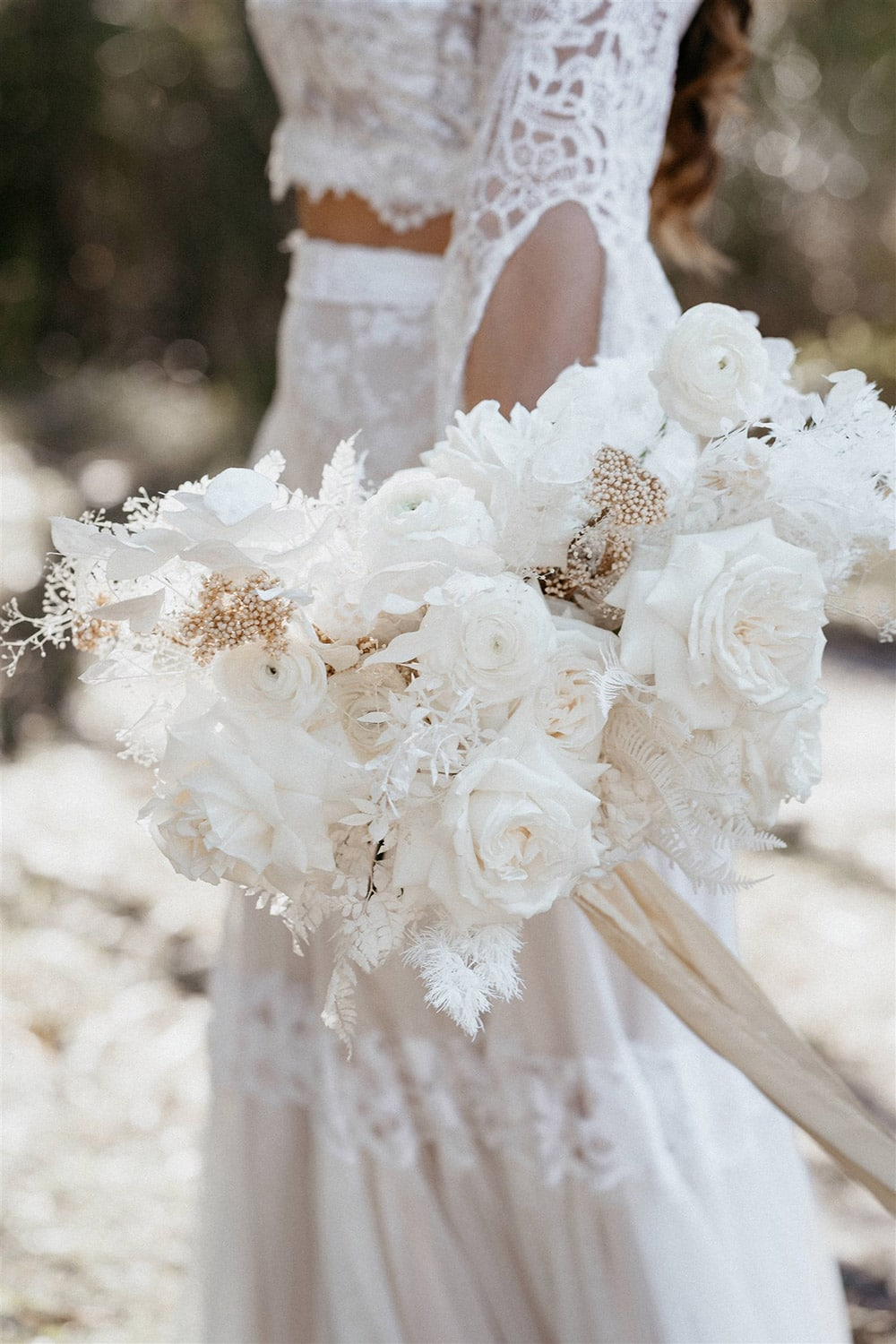Outdoor Festival Bohemian Wedding Inspiration   This boho bride carries a beautiful white monochromatic wedding bouquet which features ranunculus, roses, fern, silver dollar eucalyptus, ruscus, ming fern, leatherleaf fern, mini gypsophila and neutral rice flower accents tied with champagne ribbon.   Photography: Shae Estella Photo