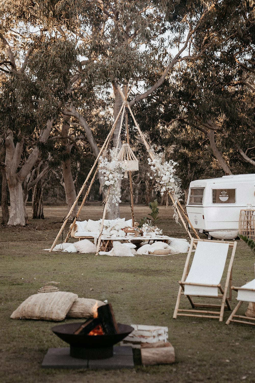 Outdoor Festival Bohemian Wedding Inspiration   A naked tipi wrapped in fairy lights and sprays of boho florals is set for picnic style grazing. Beneath a beaded and fringed chandelier sits layered rugs, scattered cushions in neutral and white textures and a low table set for eight. This is topped with a macrame runner and clusters of white vessels displaying fresh posies.   Photography: Shae Estella Photo