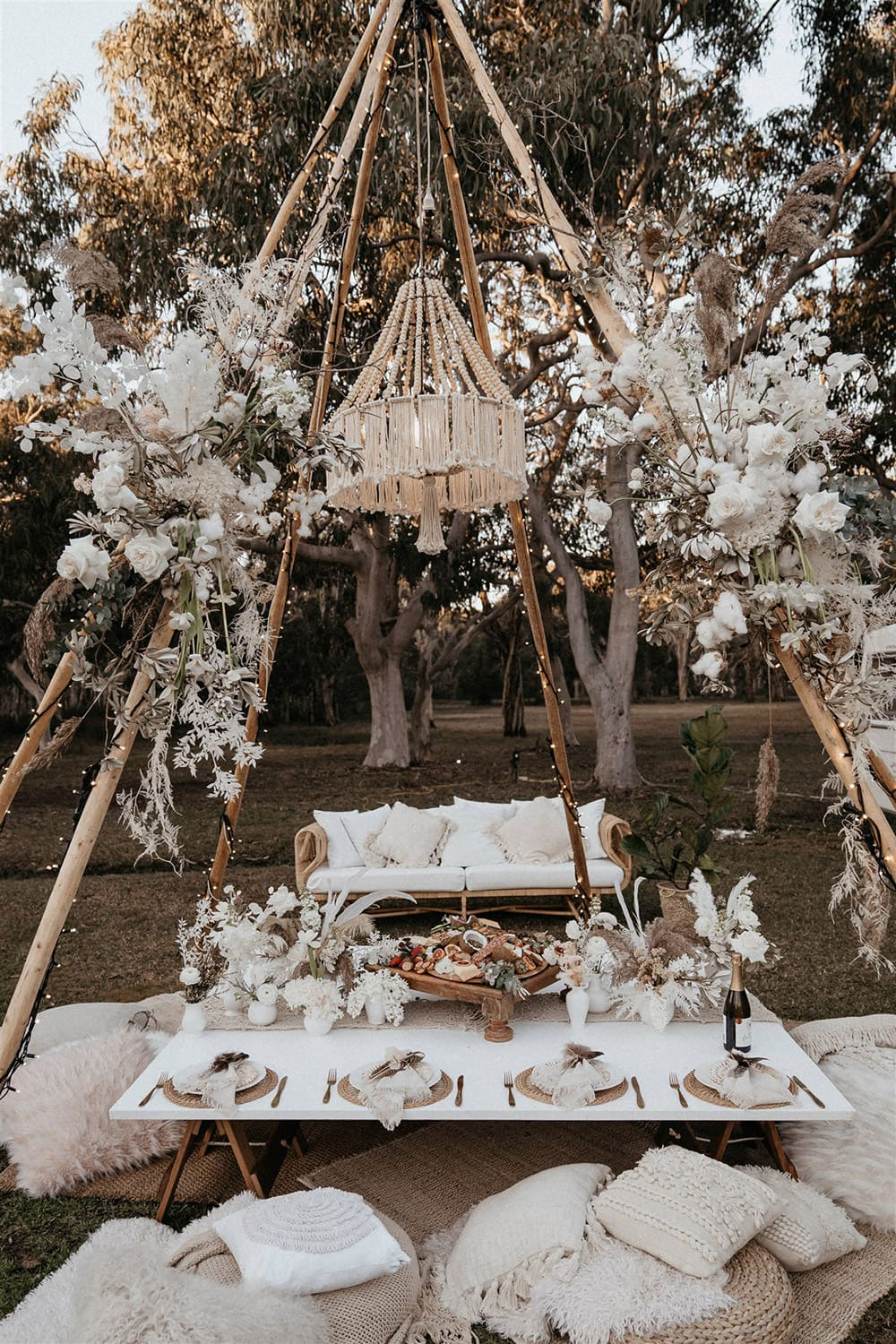 Outdoor Festival Bohemian Wedding Inspiration   A naked tipi wrapped in fairy lights and sprays of boho florals is set for picnic style grazing. Beneath a beaded and fringed chandelier sits layered rugs, scattered cushions in neutral and white textures and a low table set for eight. This is topped with a macrame runner and clusters of white vessels displaying fresh posies. The place settings feature gold cutlery, a natural woven placemat topped with white plateware and neutral napkins tied with cord and feathers. A generous antipasto platter placed in the centre of the table is ready for the happy couple and their crew!   Photography: Shae Estella Photo