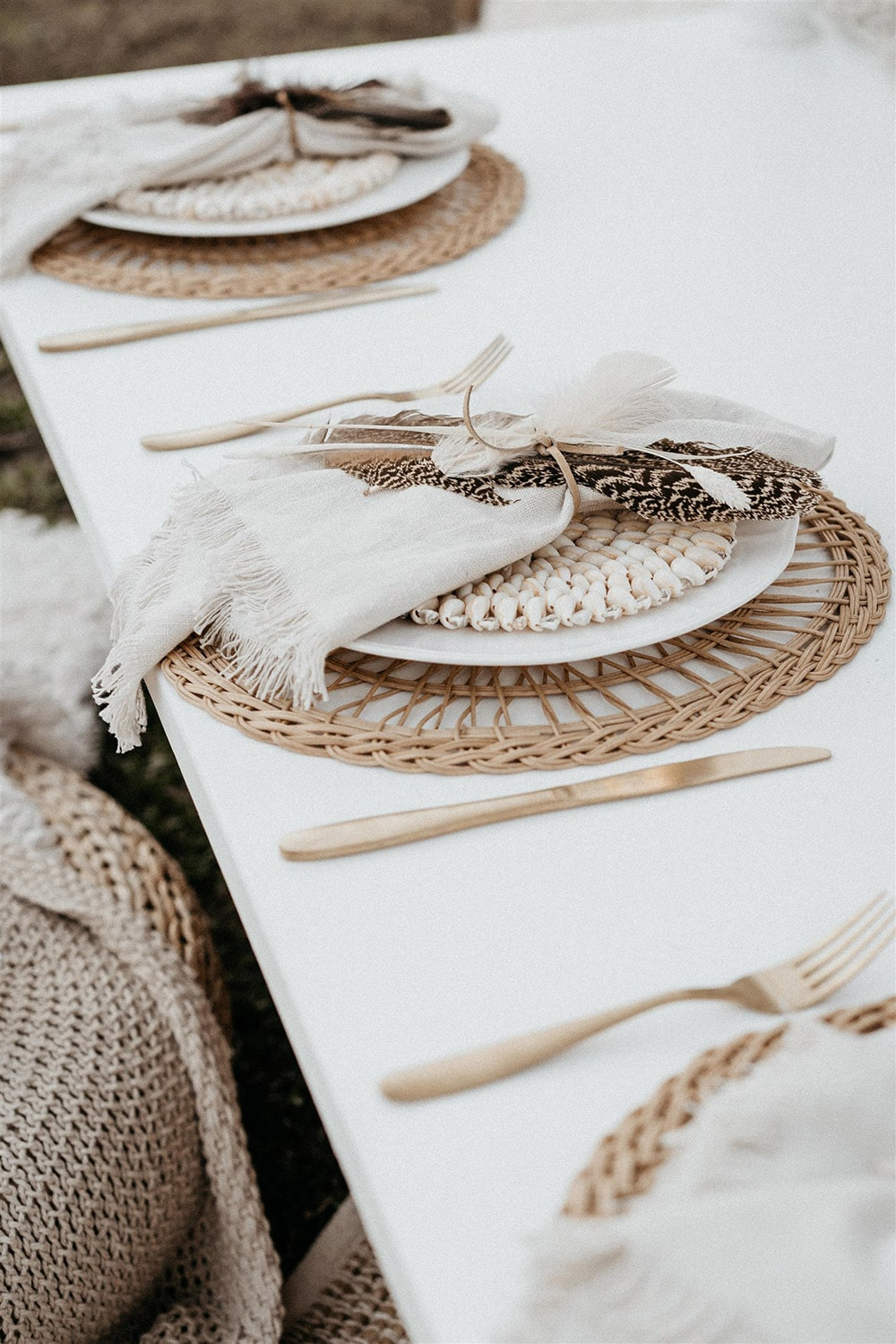 Outdoor Festival Bohemian Wedding Inspiration   The place settings feature gold cutlery, a natural woven placemat topped with white plateware and neutral napkins tied with cord and feathers.   Photography: Shae Estella Photo