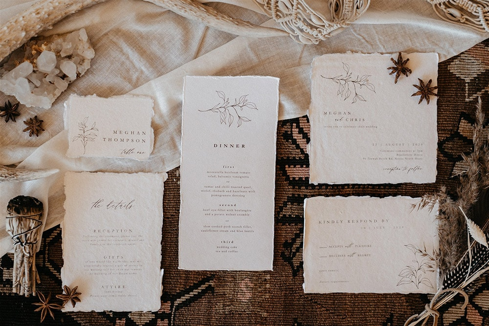 """Outdoor Festival Bohemian Wedding Inspiration   A boho wedding stationery suite on white deckle edge cotton paper features a fine line foliage motif and modern vintage serif font paired with flowing script. The suite consists of a wedding invitation, a card providing """"The Details"""" on the reception, gifts and attire, a """"Kindly Respond By"""" RSVP card, an escort card with the guest name and table number, and a dinner menu.   Photography: Shae Estella Photo"""