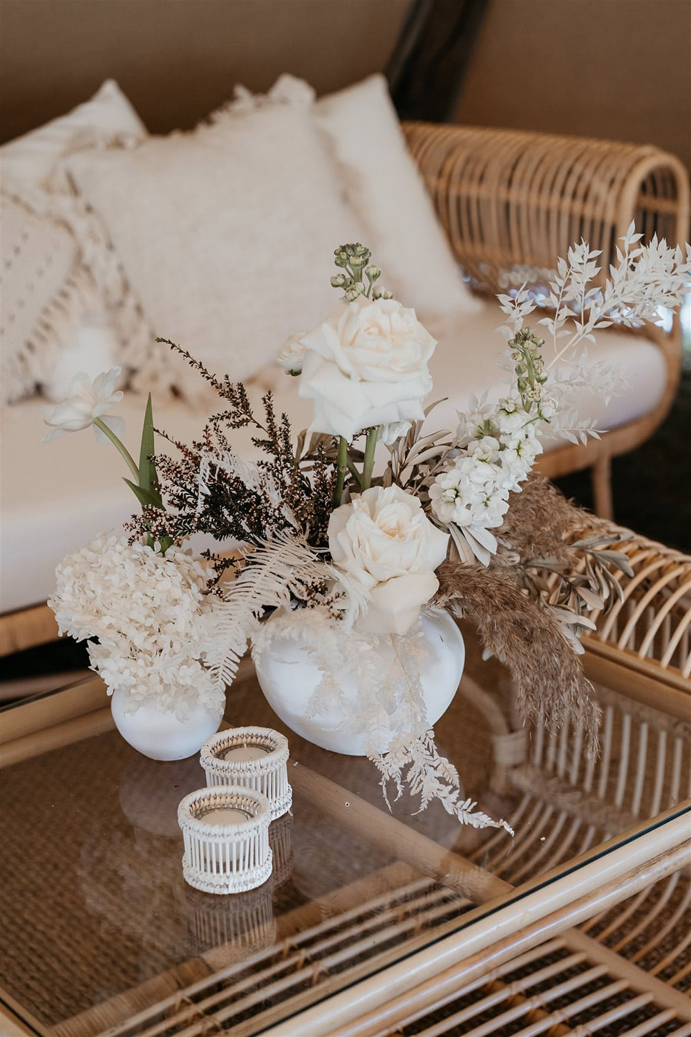 Outdoor Festival Bohemian Wedding Inspiration   ealight holders and fresh blooms in white vases. Potted plants in wicker baskets add lush greenery to this cool space.   Photography: Shae Estella Photo