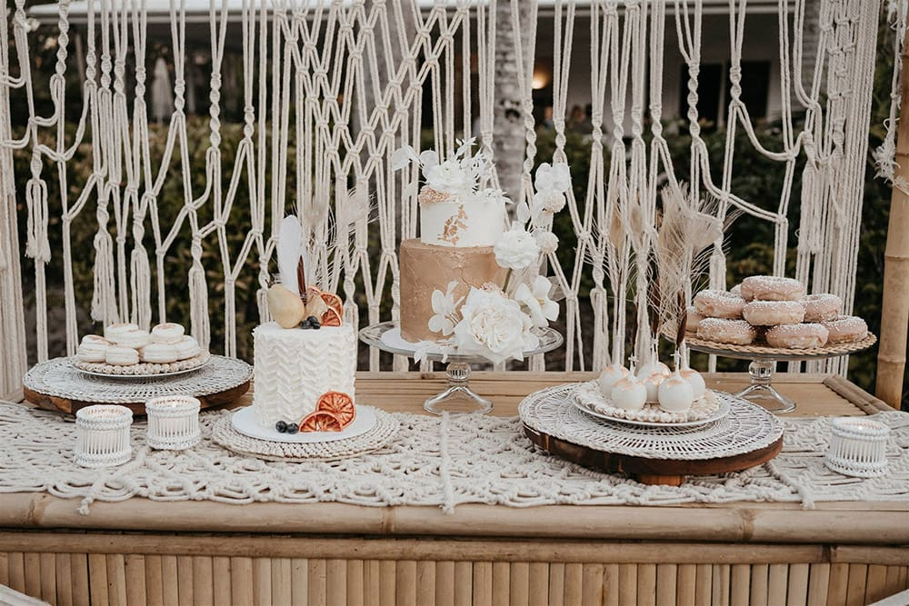 Outdoor Festival Bohemian Wedding Inspiration   For the boho wedding dessert display, a bamboo frame is dressed with an open weave macrame garland and wild neutral and white floral arrangements top right and bottom left. The variety of desserts offers something for everyone, with cakes, donuts, cake pops and macarons presented on a matching bamboo bar decorated with a macrame table runner, white bamboo tealight holders and neutral fabric bunting.   Photography: Shae Estella Photo